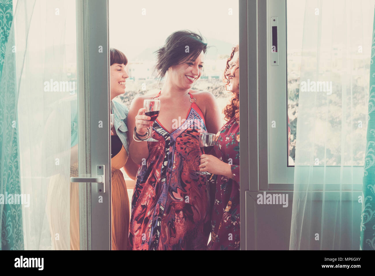 group of three caucasian beautiful friends woman females at home celebrate and in nice leisure activity. friendship with smiles and enjoying the time  - Stock Image
