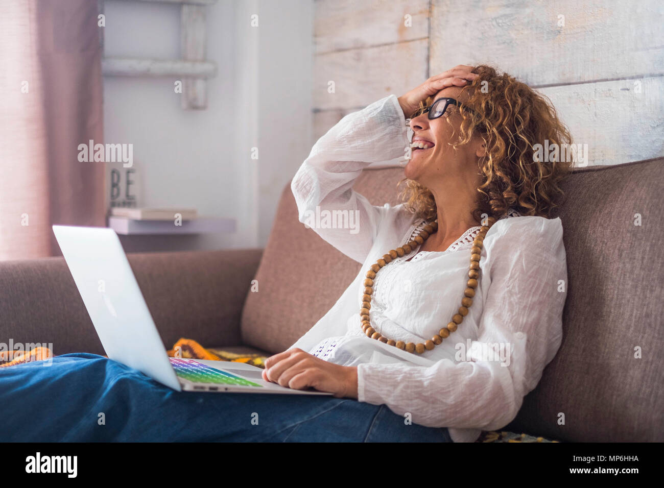 smile and laughing caucasian beautiful middle age woman sit down on the sofa at home with a colored keyboard laptop. working happy independent concept - Stock Image