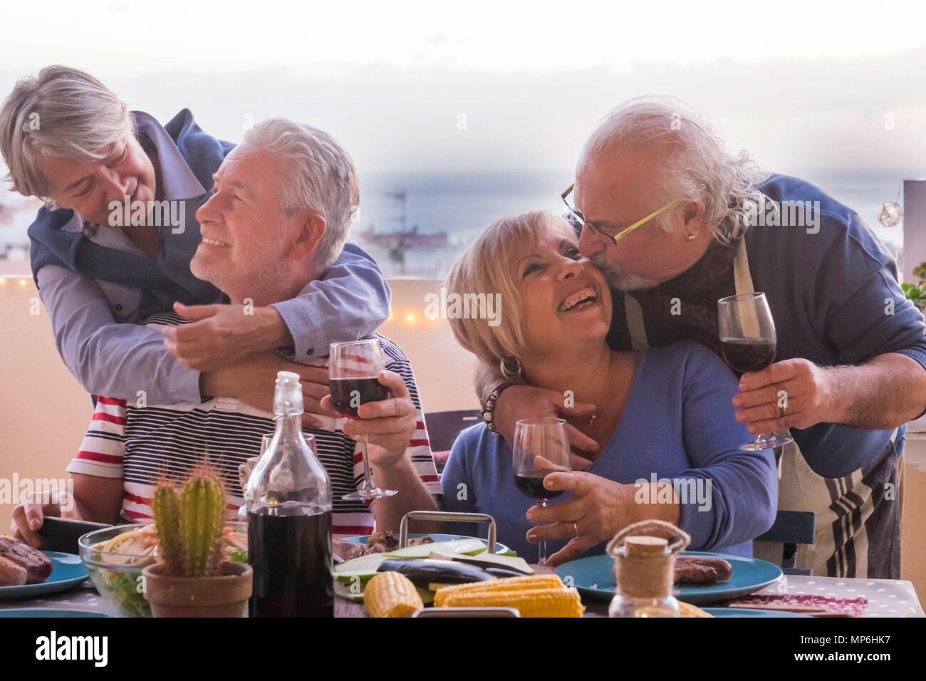 two mature couple stay together with love smiles and kisses during a dinner outdoor on the terrace rooftop with ocean and roofs view. joy and having f - Stock Image