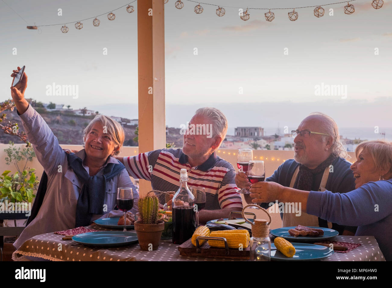 group of adults friends elderly retired having fun taking a picture like selfie all together during a dinner outdoor on the terrace rooftop. celebrate - Stock Image