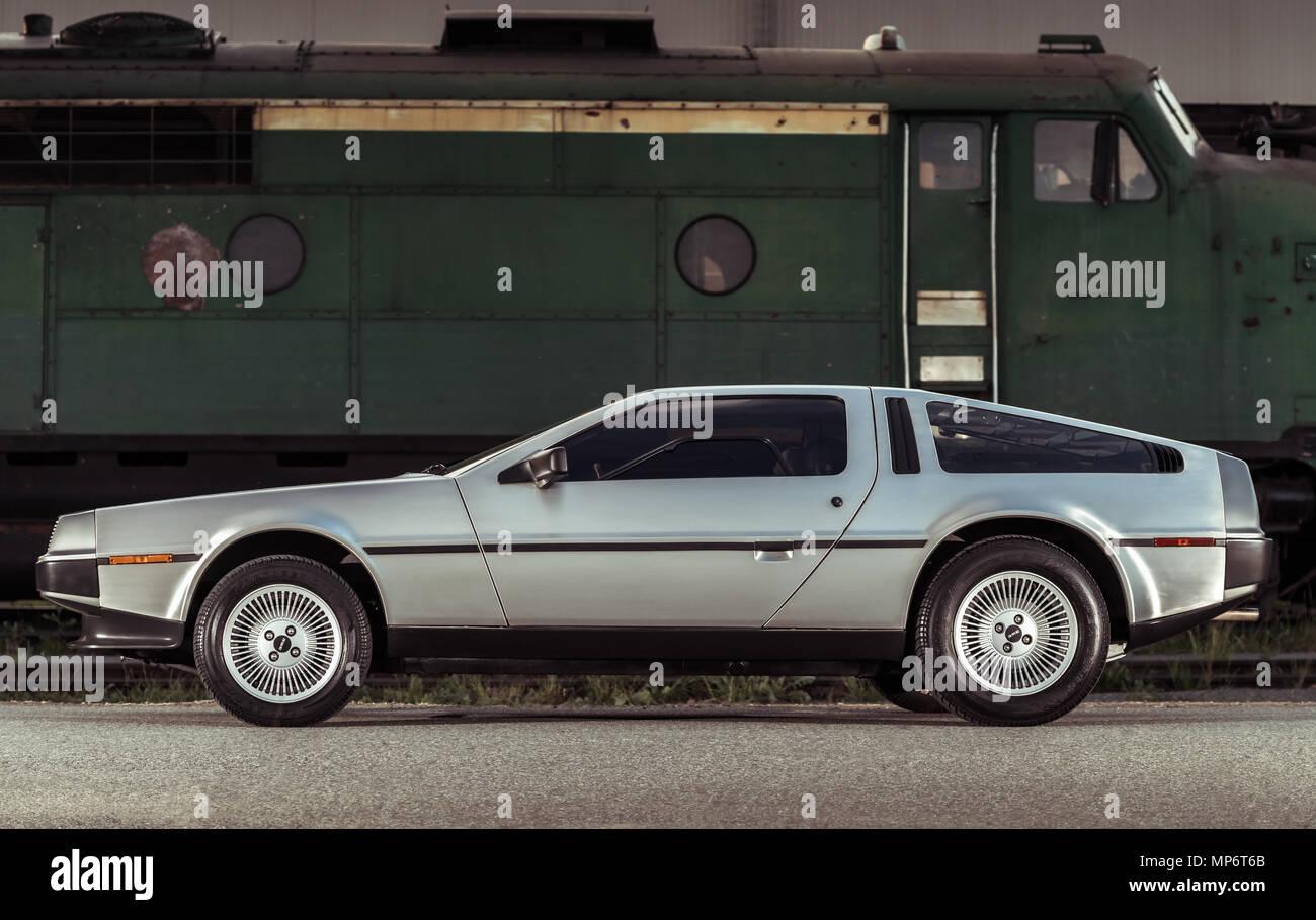 Adelaide, Australia - September 7, 2013: Legendary DeLorean DMC-12 stainless steel car parked next to train on street - Stock Image