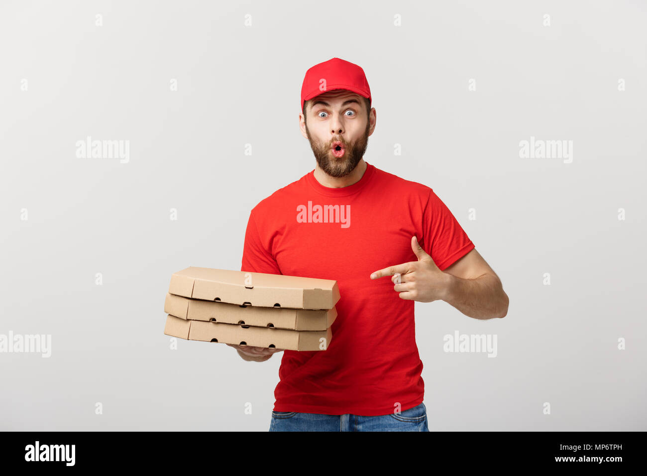 Delivery Concept: Portrait of Pizza delivery man presenting something in box. Isolated white background. - Stock Image