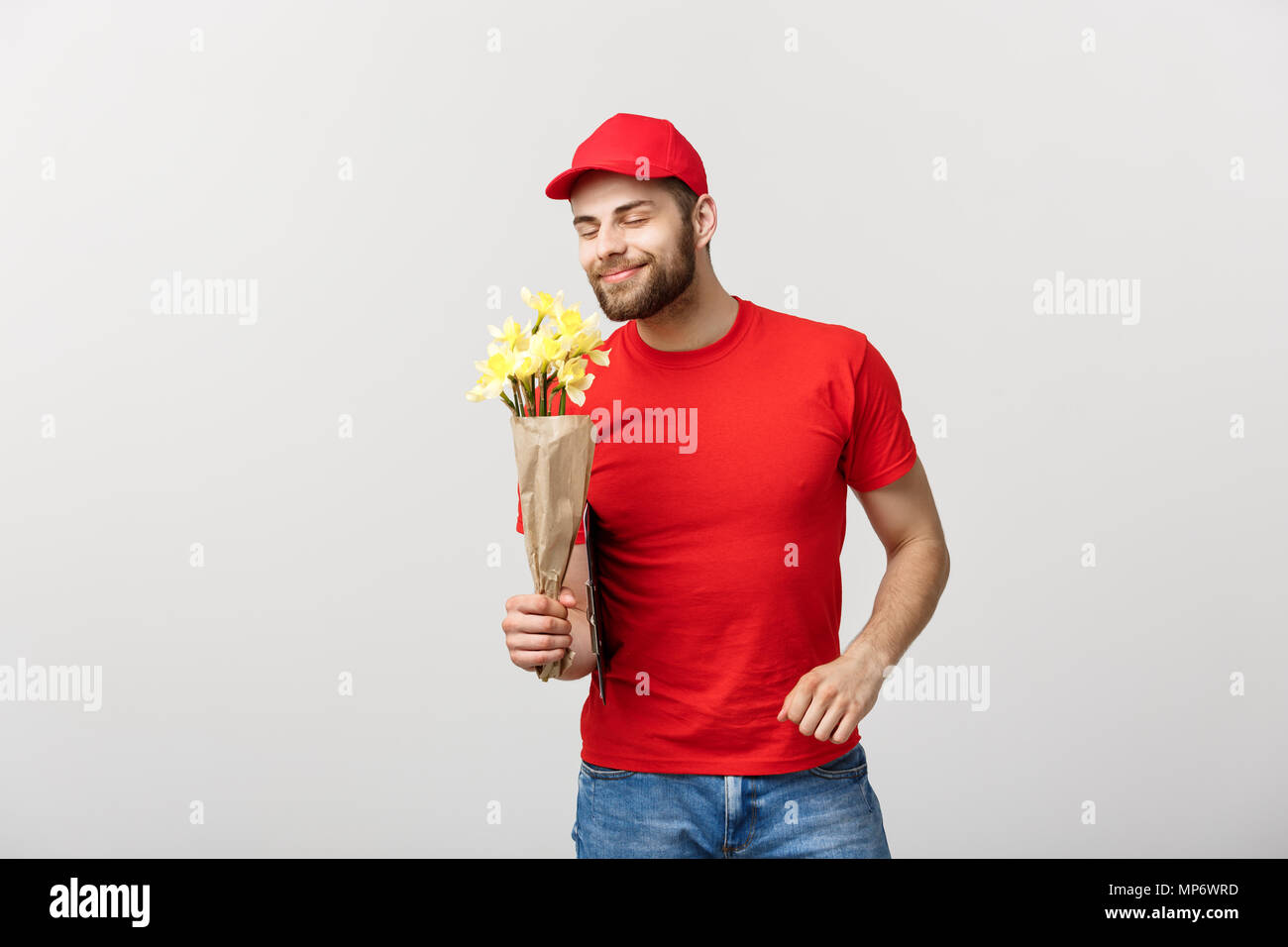 72fc3023790 Delivery Concept  Portrait of happy flower delivery man holding beautiful  bouquet flower and pointing finger