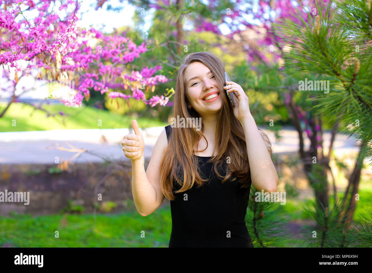 Young female person talking by smartphone and showing thumbs up in spring park. - Stock Image