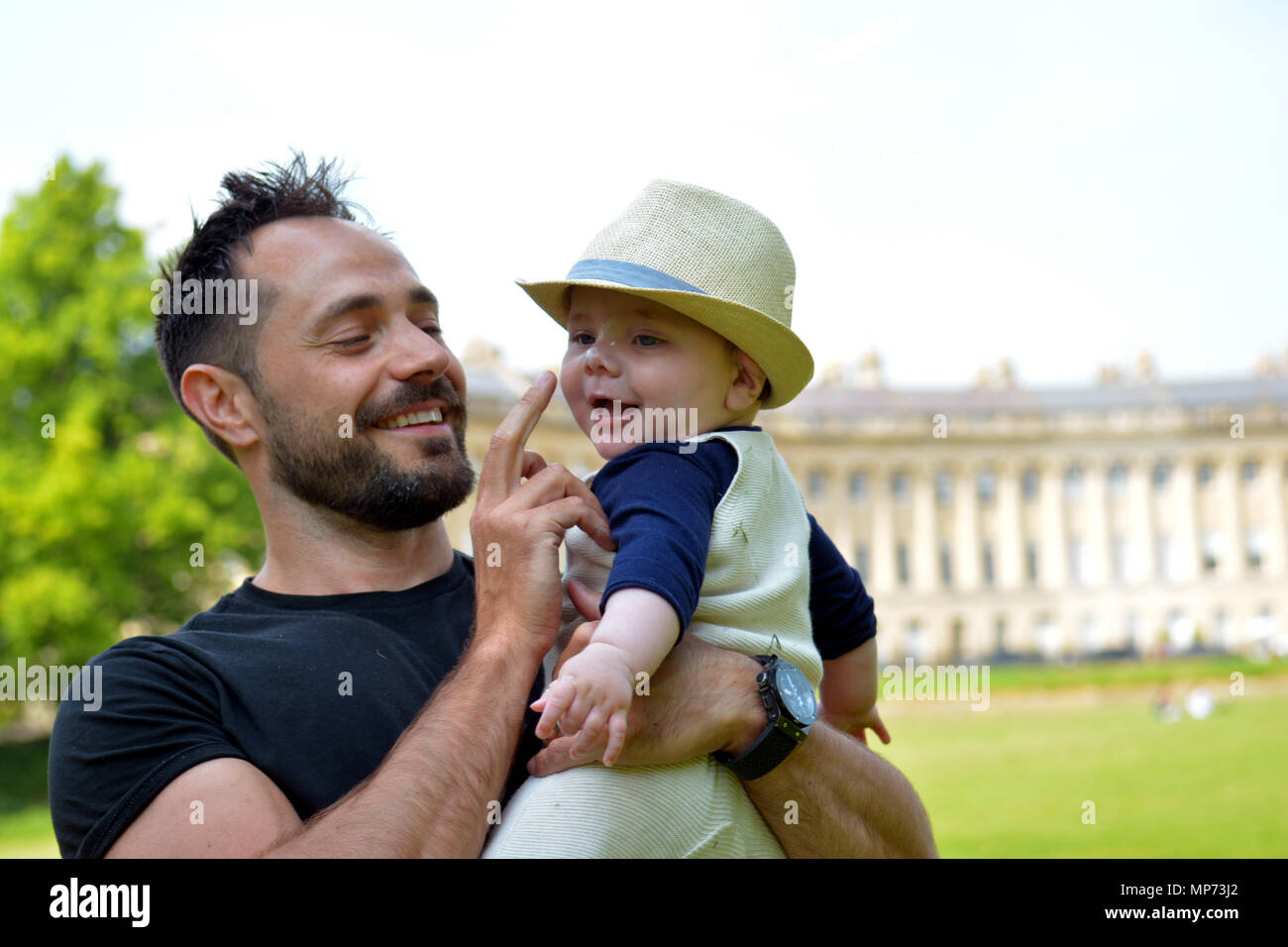 UK Weather. Oskar and his son Noah who is 8 months old enjoying a Dab of Suntan lotion popped on his nose at the grassy lawns of World Famous Bath Royal Crescent with 30 terraced houses laid out in a sweeping surround.  Robert Timoney/Alamy/Live/News - Stock Image