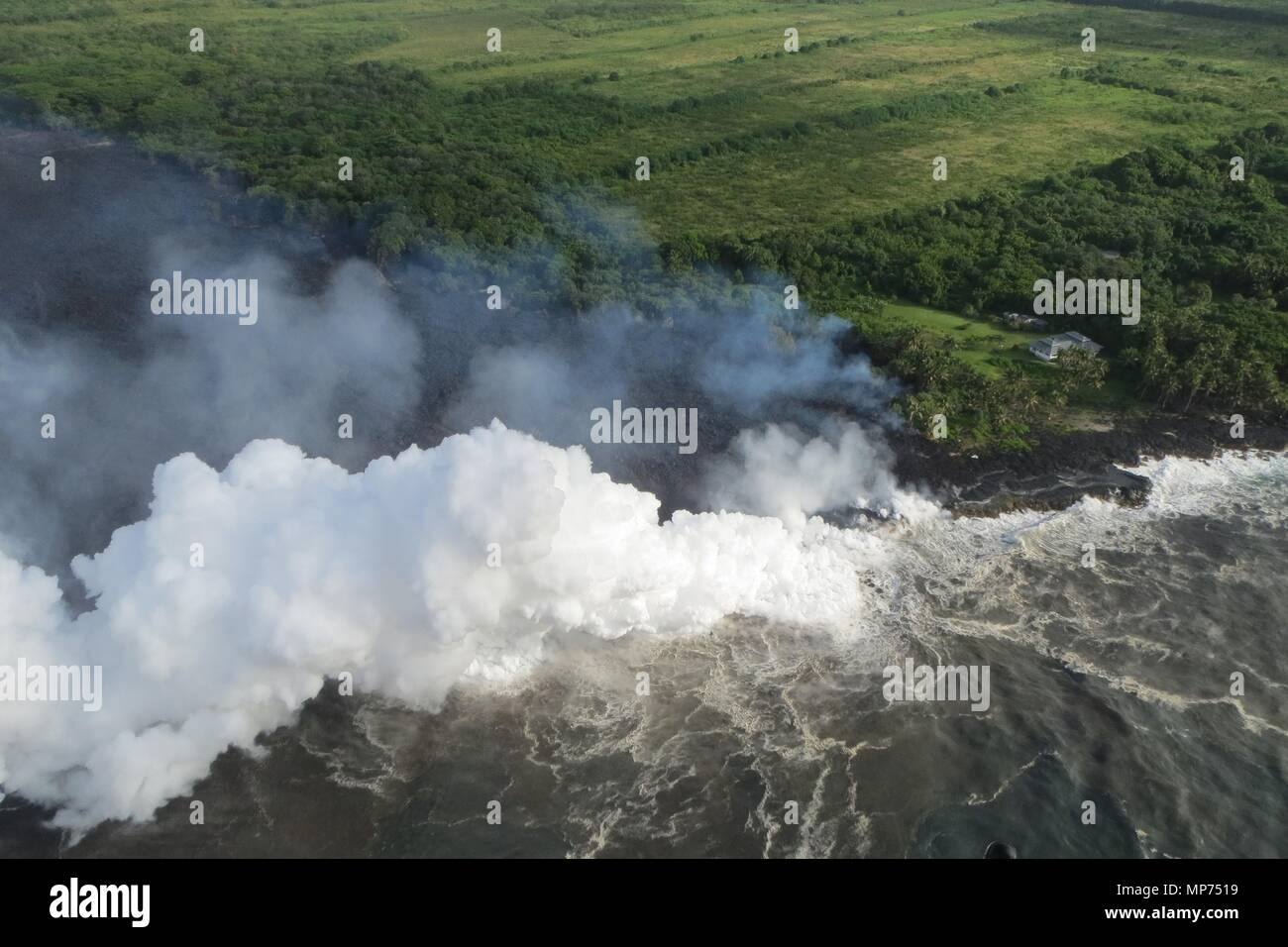 Hawaii, USA. 20th May 2018. Lava and poisonous sulfur dioxide plumes rise from fissure 20 as the molten magma reaches the ocean from the eruption of the Kilauea volcano May 20, 2018 in Pahoa, Hawaii. Hot lava entering the ocean creates a dense white plume called 'laze' (short for 'lava haze'). Laze is formed as hot lava boils seawater to dryness. Credit: Planetpix/Alamy Live News - Stock Image