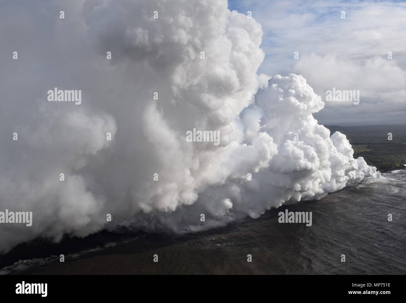 "Hawaii, USA. 20th May 2018. Lava and poisonous sulfur dioxide plumes rise from fissure 20 as the molten magma reaches the ocean from the eruption of the Kilauea volcano May 20, 2018 in Pahoa, Hawaii. Hot lava entering the ocean creates a dense white plume called ""laze"" (short for ""lava haze""). Laze is formed as hot lava boils seawater to dryness. Credit: Planetpix/Alamy Live News Stock Photo"