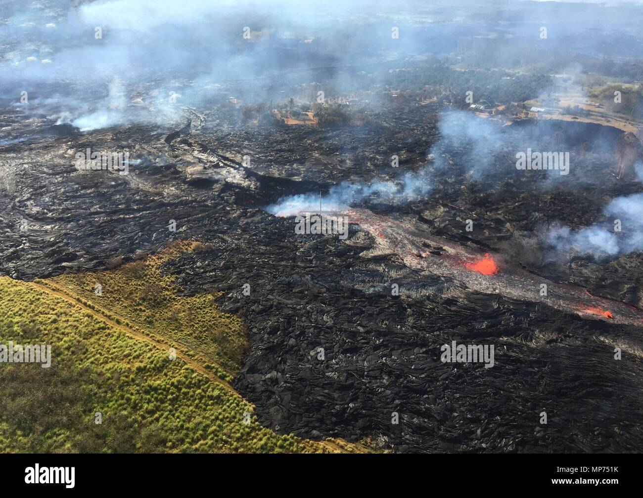 Hawaii, USA. 20th May 2018. Channelized lava streams down fissure 20 into a massive ground crack from the eruption of the Kilauea volcano May 20, 2018 in Pahoa, Hawaii. Credit: Planetpix/Alamy Live News - Stock Image
