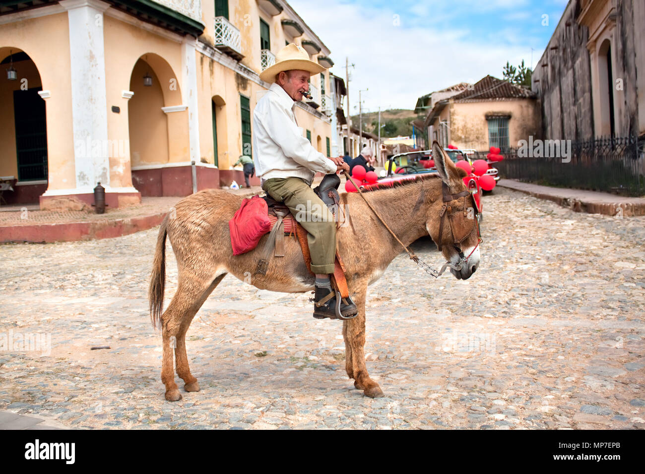 TRINIDAD CUBA, 14 JANUARY: Old men with cigar and donkey for rent in the street of colonial town Trinidad. Working in tourism is the only way cuban pe Stock Photo