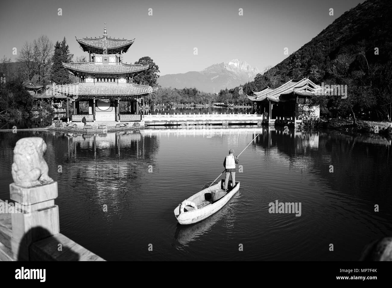 An old man on the boat in the Black Dragon Pool (Old town of Lijiang, Yunnan, China) - Stock Image