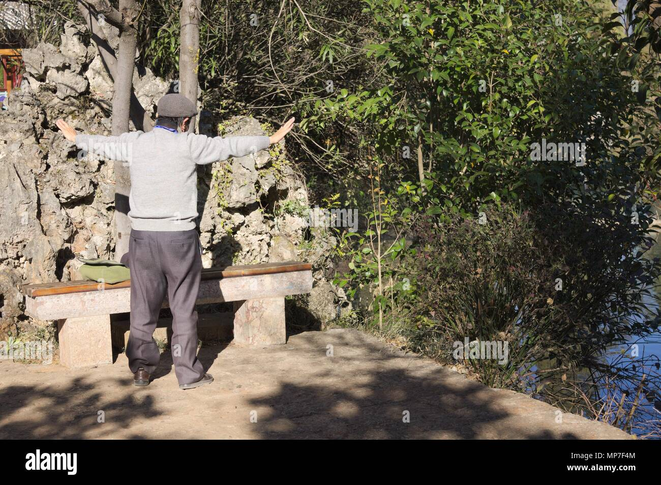 An old man is doing physical exercises in the wood (Lijiang, Yunnan, China) - Stock Image