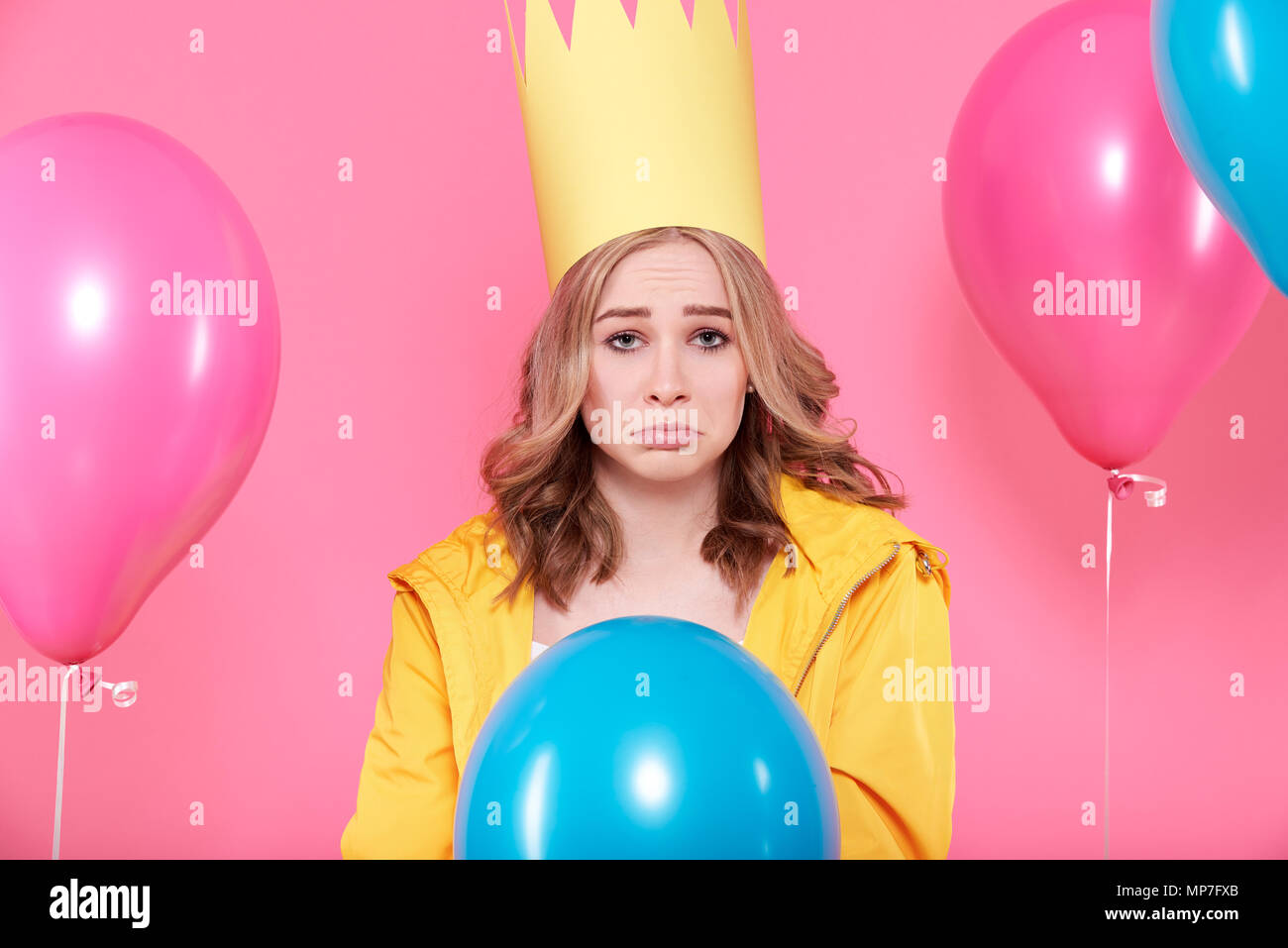 Disappointed young woman in party hat surrounded by colorful balloons, isolated over pastel pink background. Sad Birthday Party concept. - Stock Image
