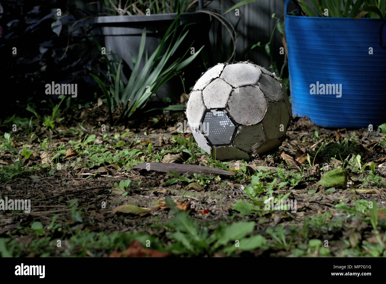 Torn up old soccer ball lay on grass. Worn out football. Concept of inactive person or useless object. - Stock Image