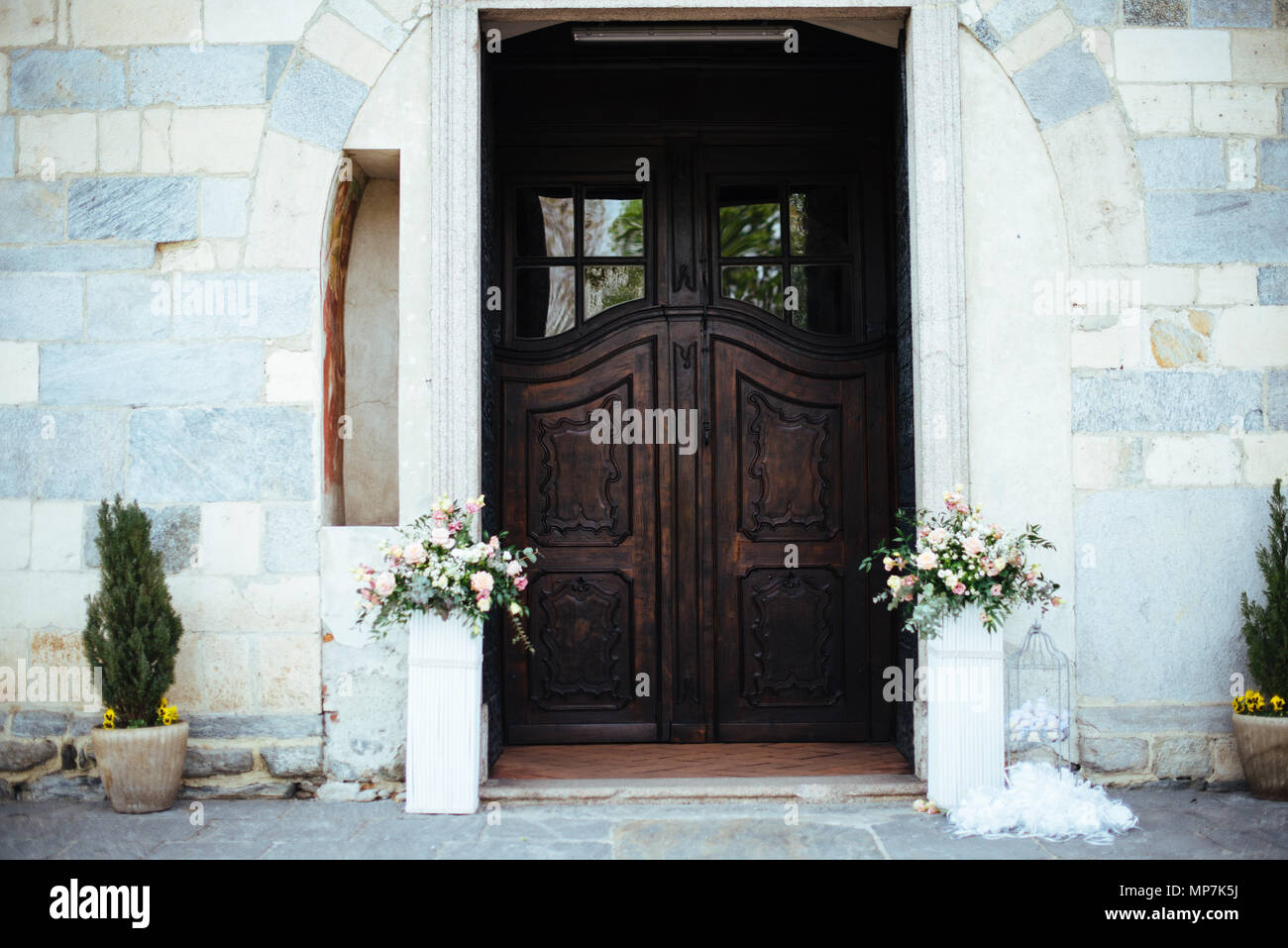 Gate Of A Romanesque Church With Flower Vases On The Sides