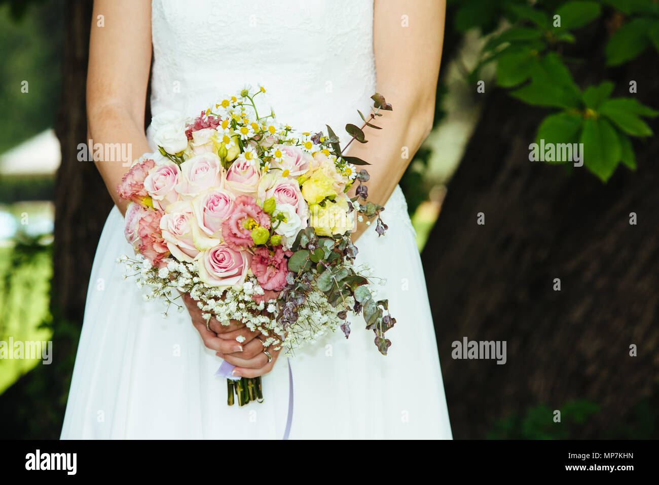 Bride Holds Her Bouquet Of Flowers With Ivy Roses Daisies And