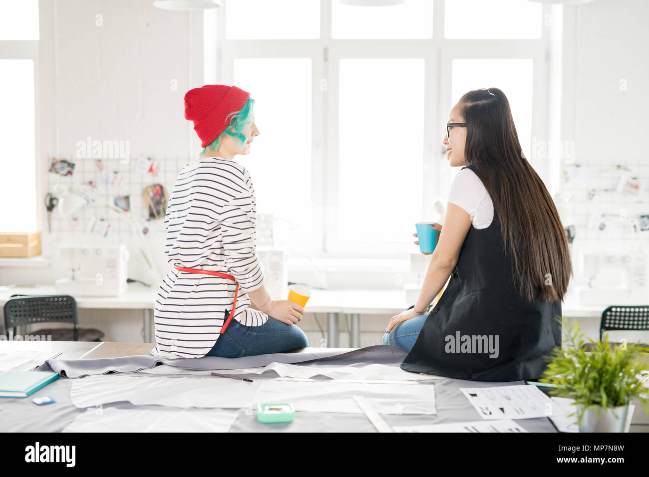 Two Fashion  Designers Chatting at Work - Stock Image