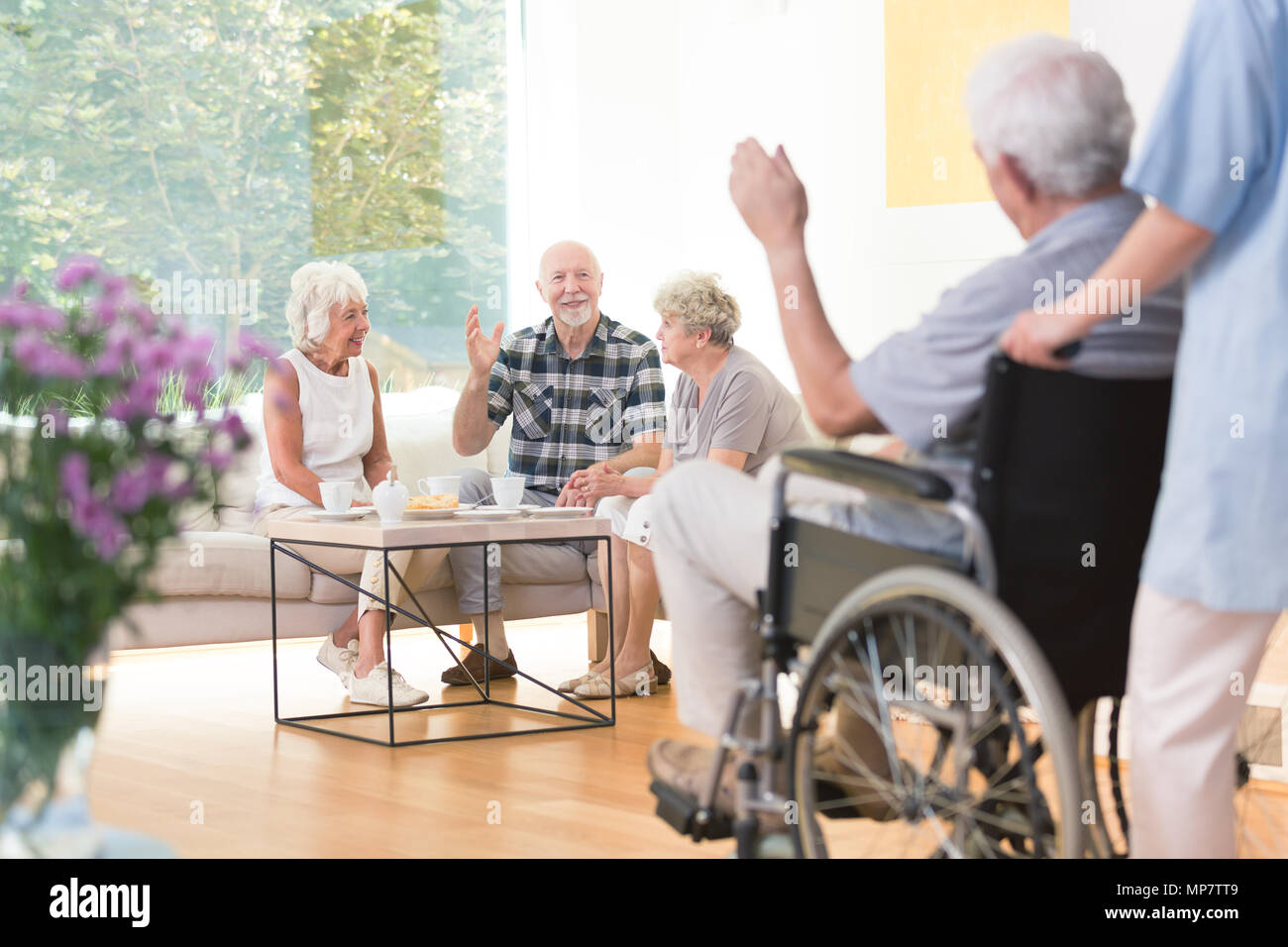 Group of senior people welcoming a friend while sitting together in living room Stock Photo