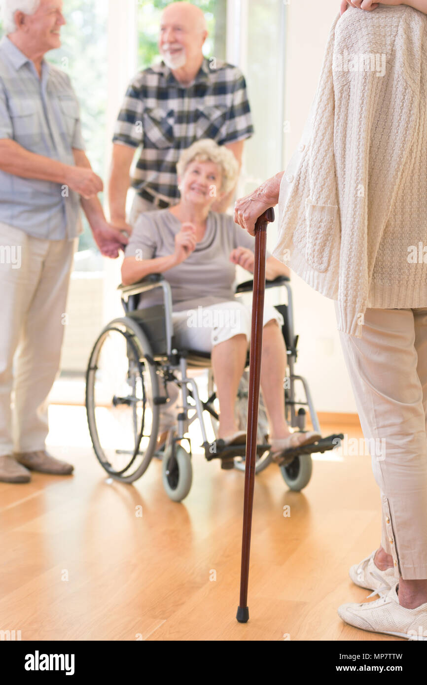 Senior person with a walking stick during meeting with friends in nursing house Stock Photo