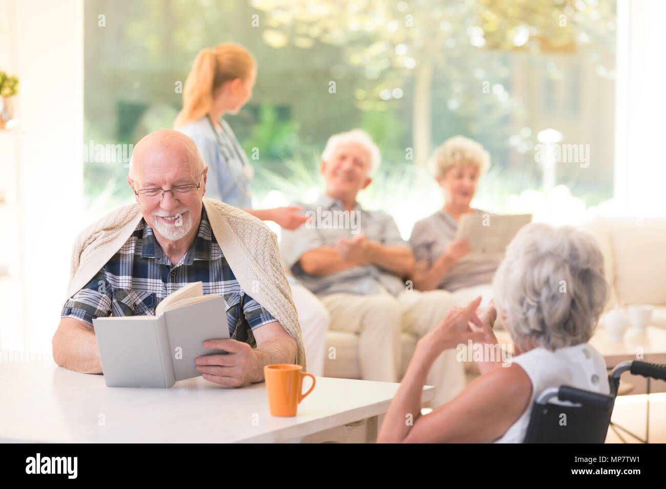 Senior man reading a book and smiling while sitting with a friend at a table in nursing house Stock Photo