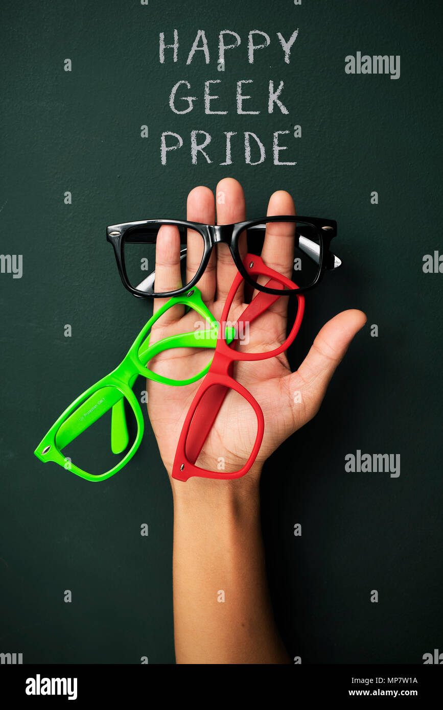 some plastic-rimmed eyeglasses of different colors in the hand of a young man and the text happy geek pride against a dark green surface - Stock Image