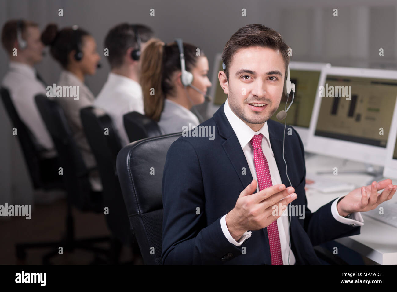 Shot of a young hotline consultant solving his client's problem Stock Photo