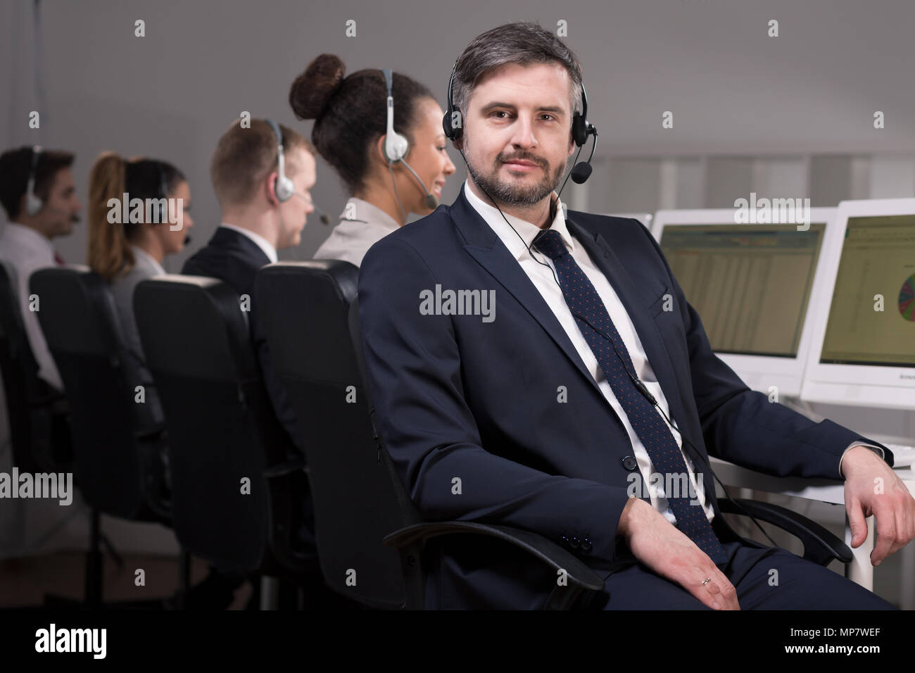 Man in suit with headset working in call center Stock Photo
