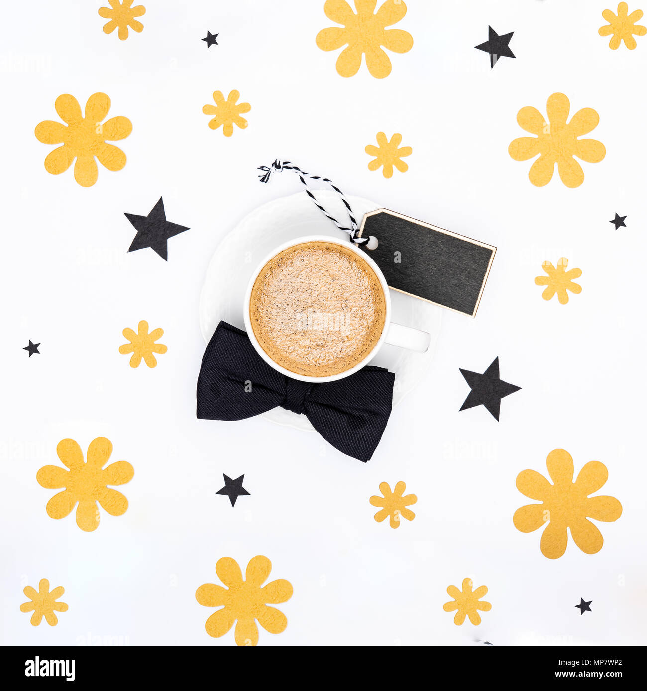 Happy Father's Day Background. Cup of coffee and black bow tie on white background flat lay. Floral Fathers day still life setup. - Stock Image
