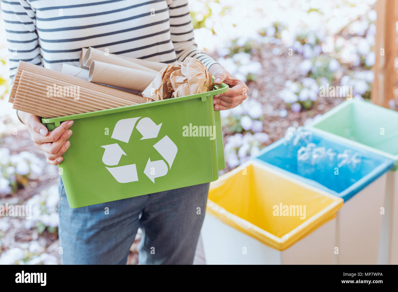 Activist taking care of environment, sorting paper waste to proper recycling bin on terrace Stock Photo