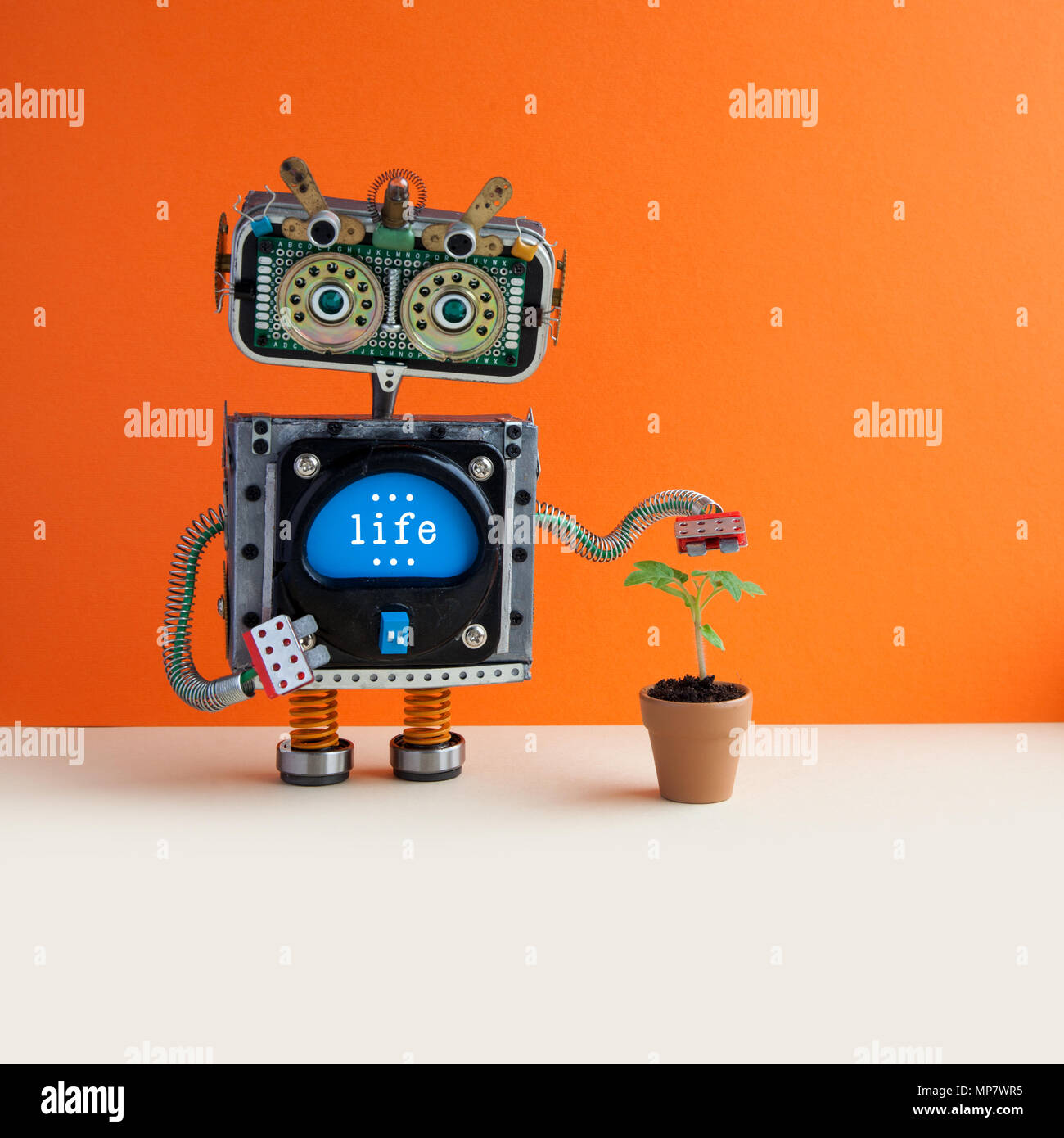 Organic eco life concept. Robot with a small green sprout plant in a clay flower pot. Orange wall background, copy space. - Stock Image
