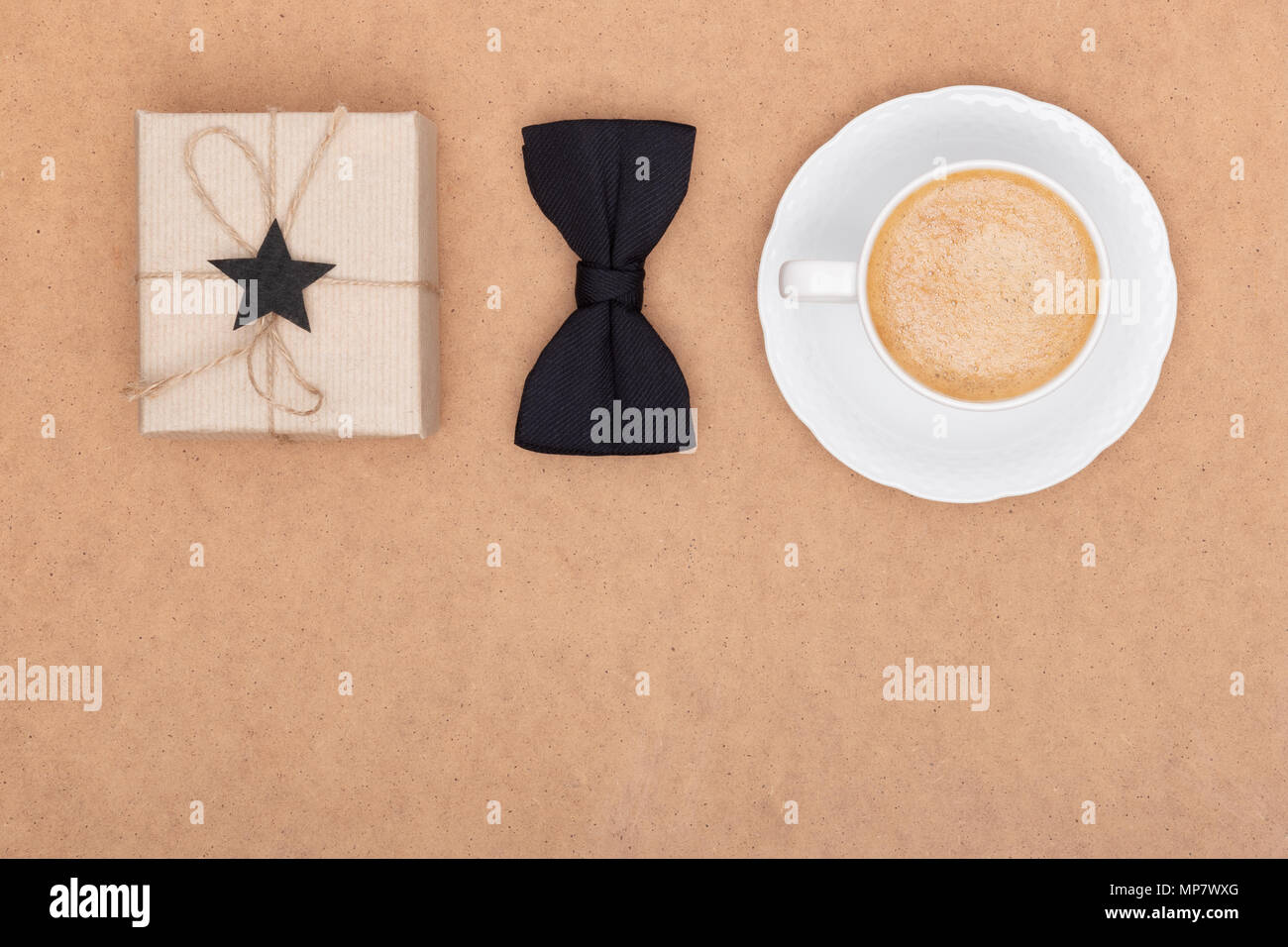 Happy Father's Day Background. Cup of coffee, beautiful present and black bow tie on brown background flat lay. Fathers day still life setup. - Stock Image