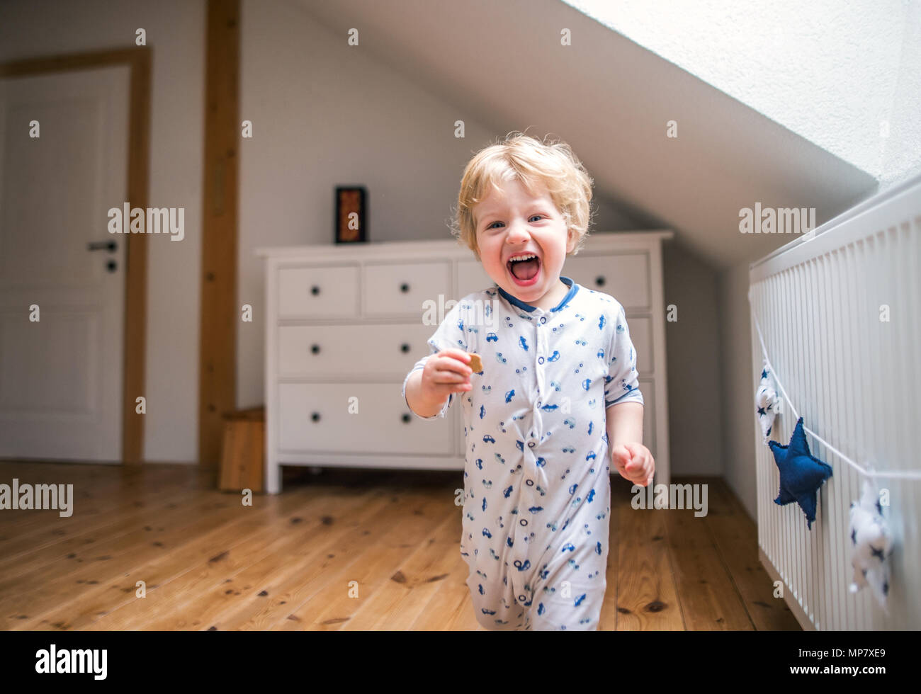 A toddler boy in the bedroom at home. - Stock Image