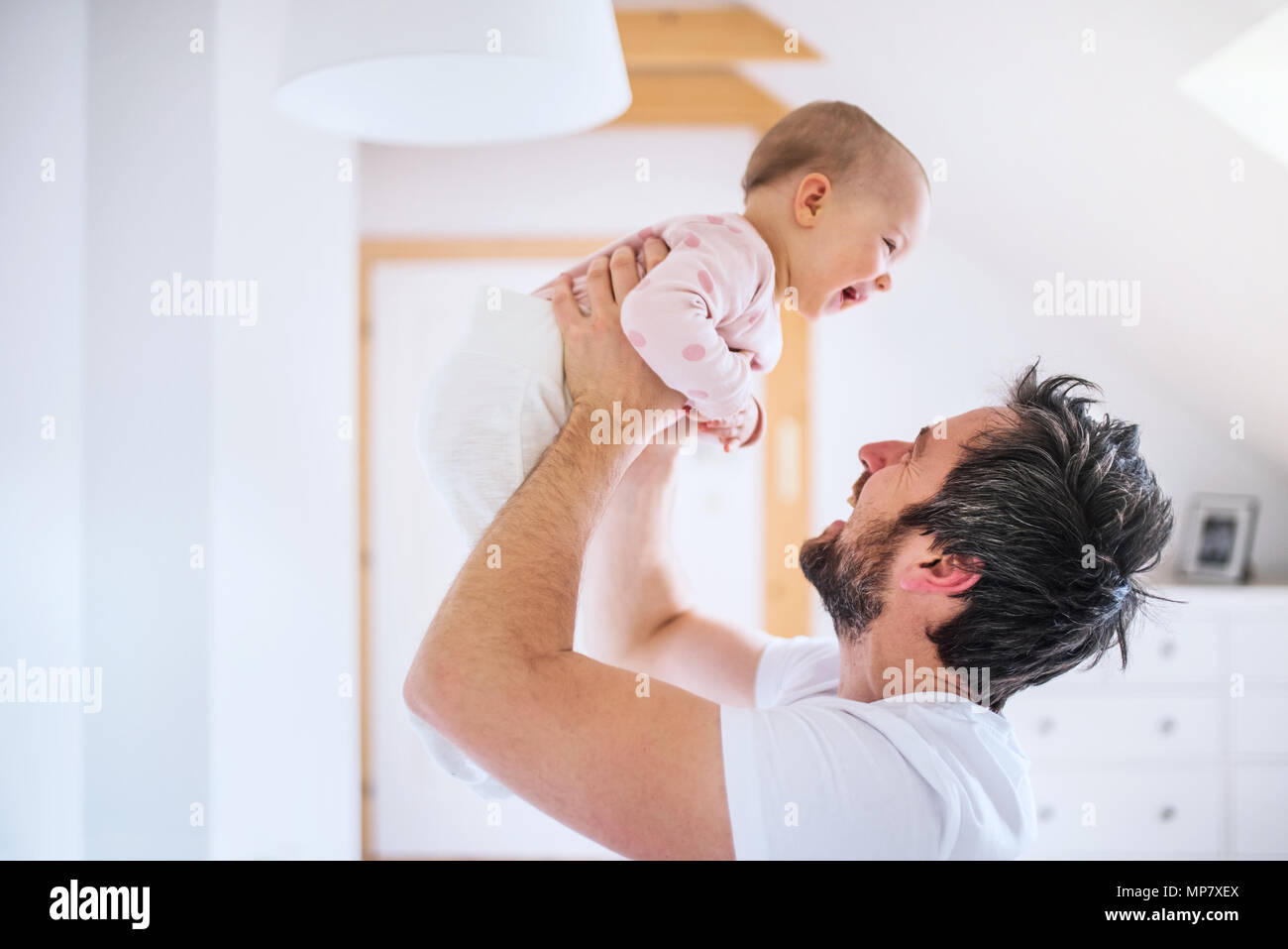 Father with a toddler girl in bedroom at home, having fun. - Stock Image