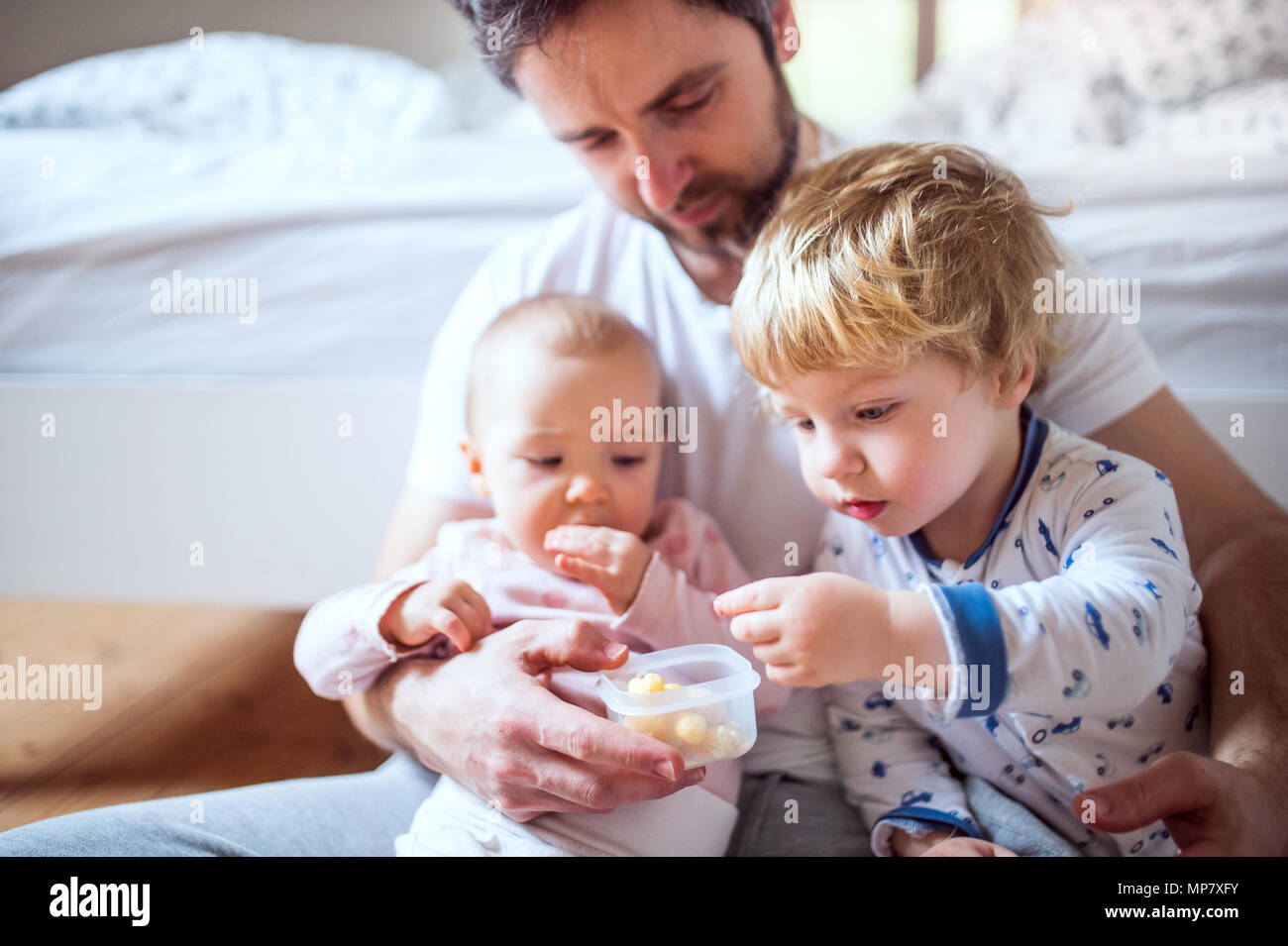 Father with toddler children eating finger food in bedroom at home. - Stock Image