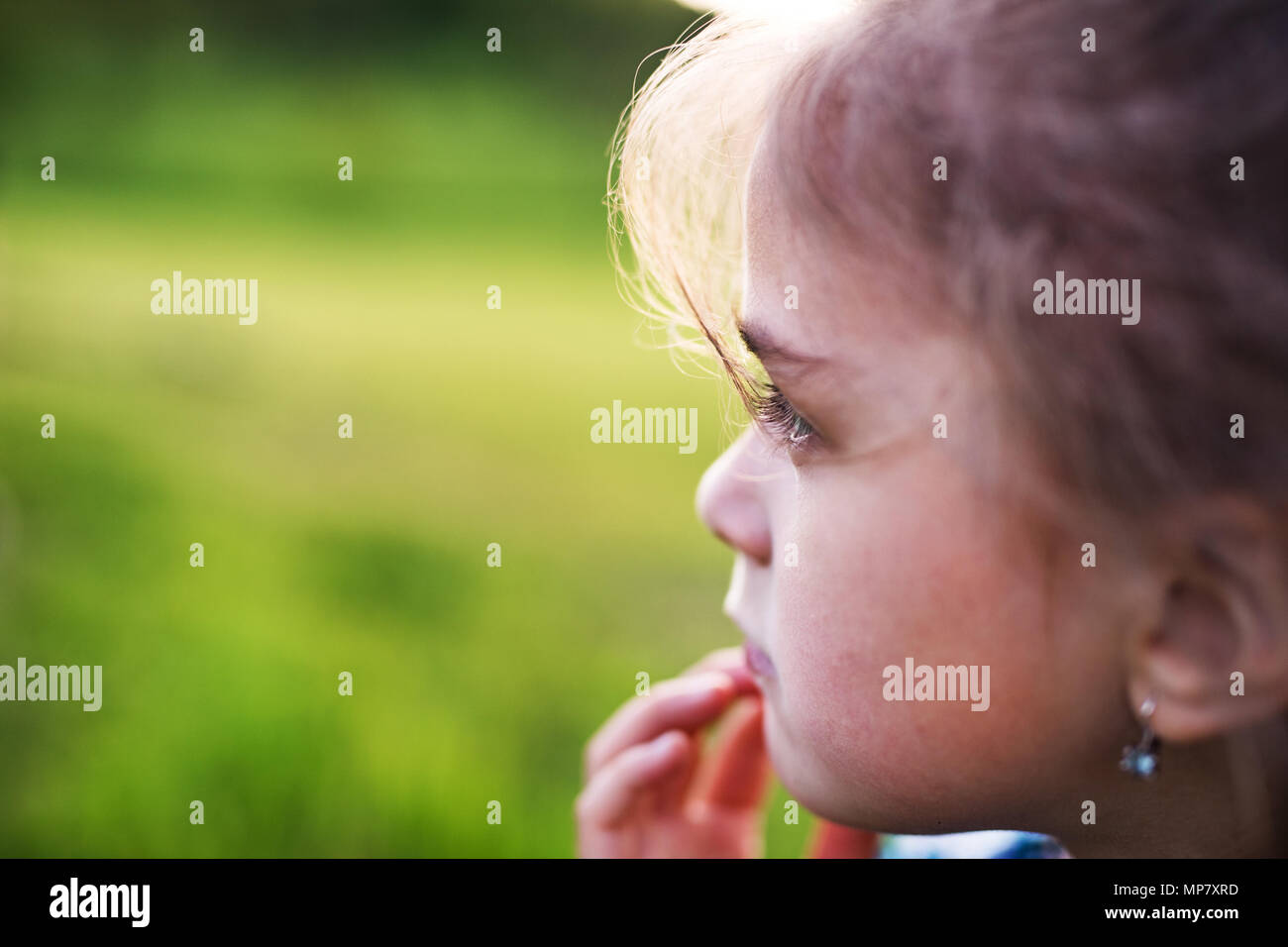 A small girl in the garden in spring nature. Copy space. - Stock Image