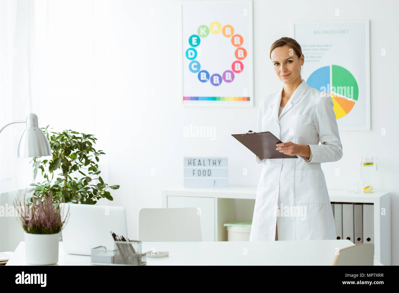 Professional nutritionist in white uniform in the office with plant and colorful posters - Stock Image