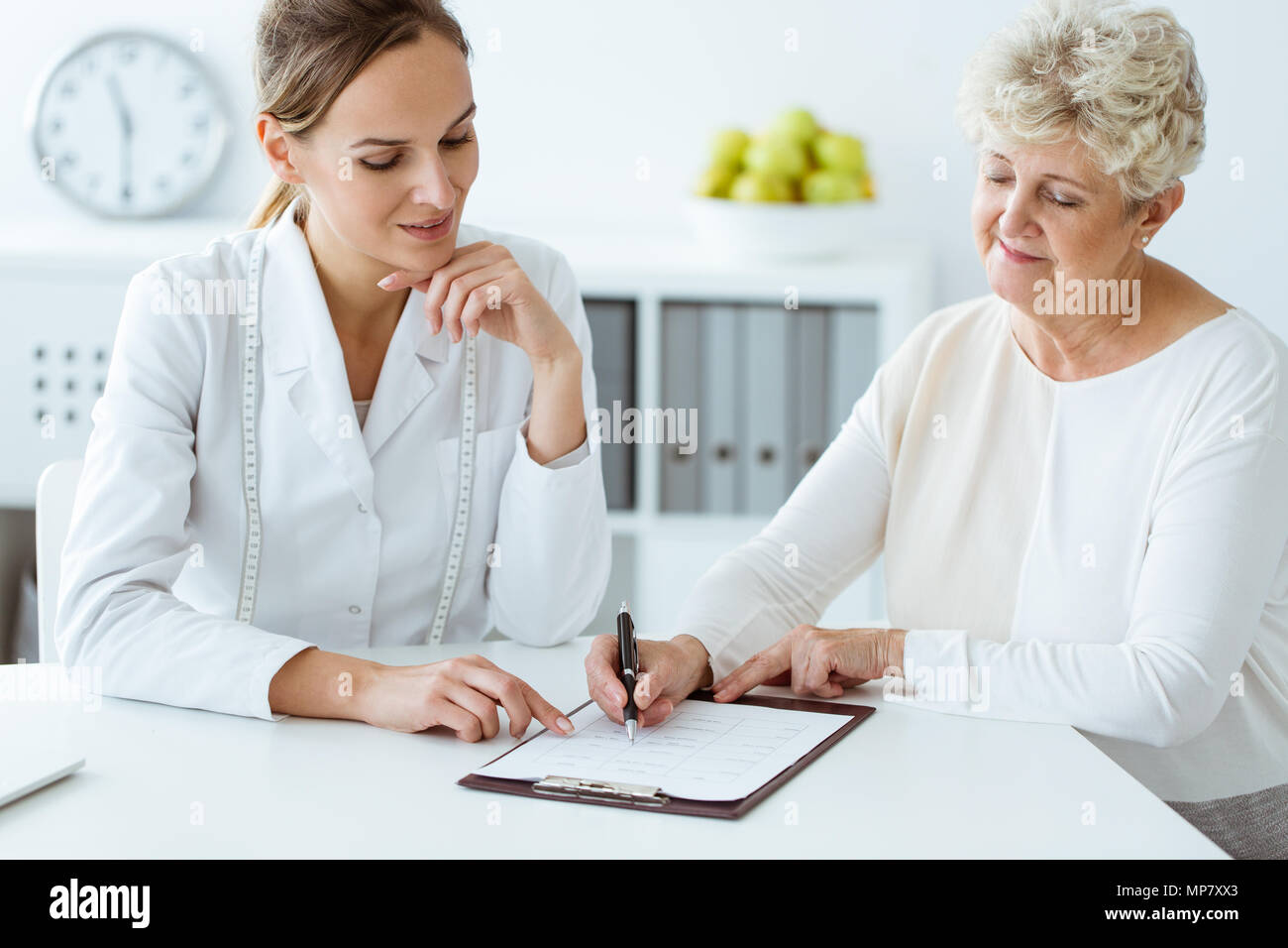 Dietician and diabetic patient with measure tape discussing daily healthy diet at the hospital - Stock Image
