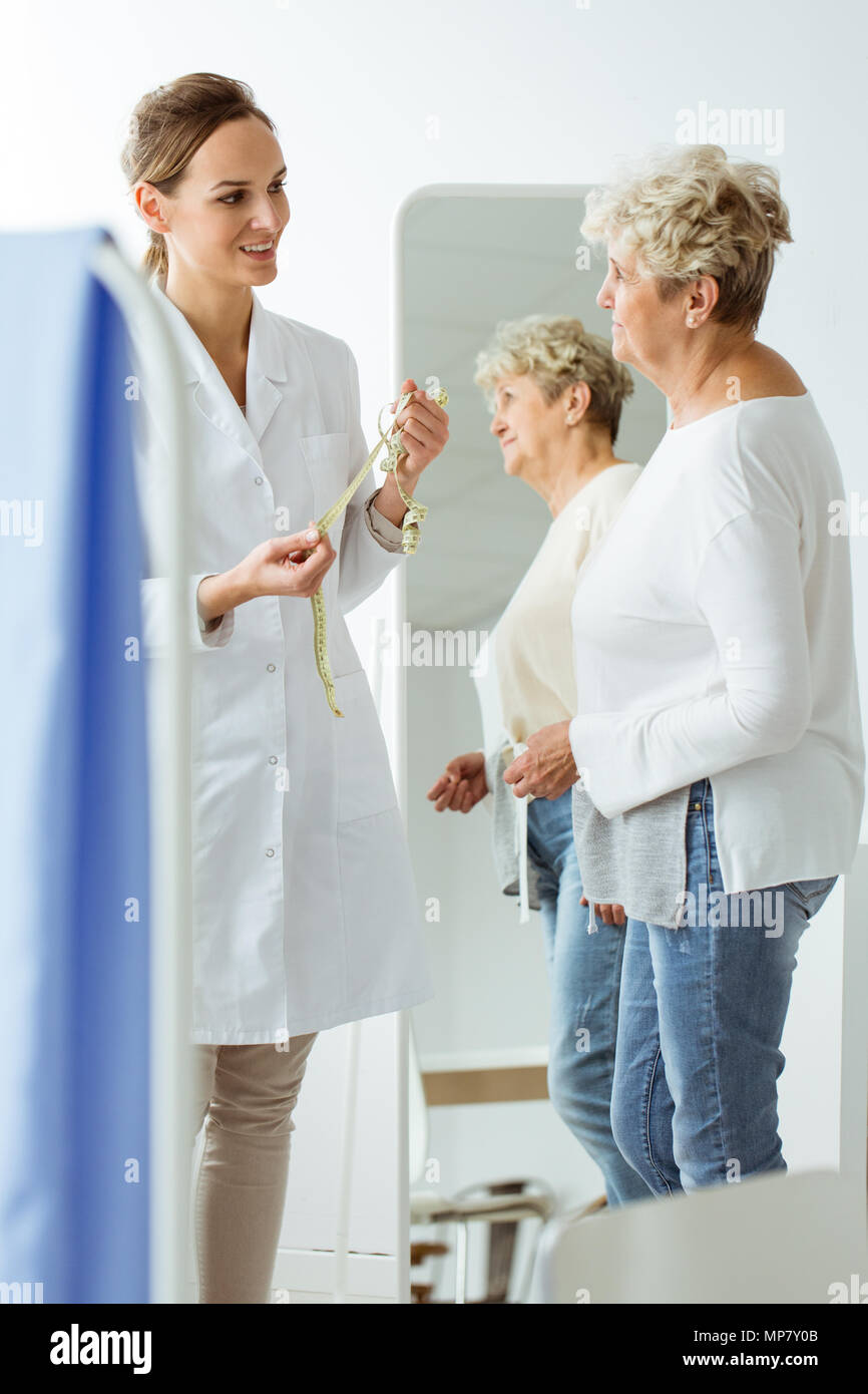 Patient with nutritional problem standing in front of a mirror next to a dietician with measuring tape - Stock Image