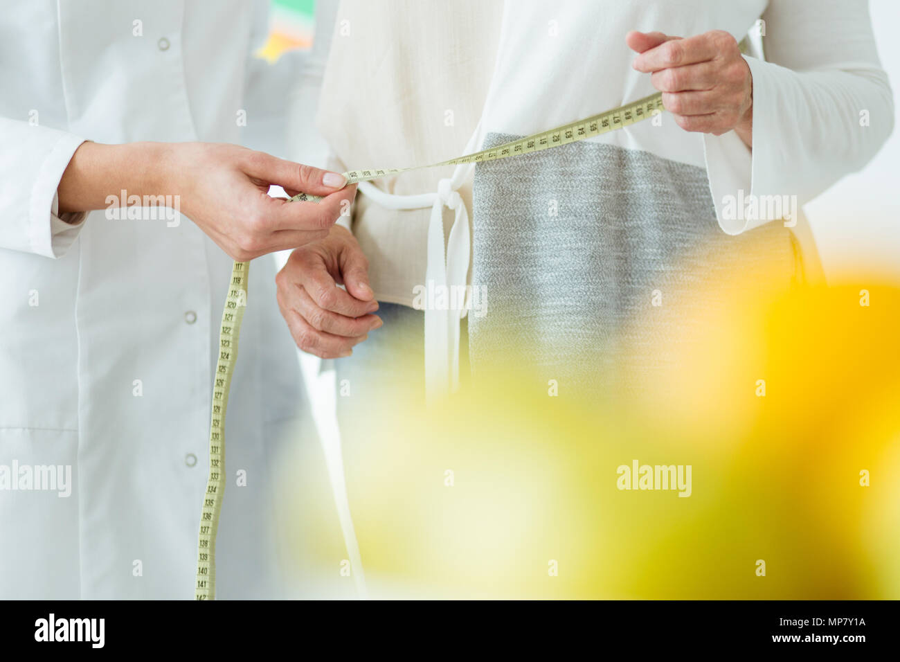 Close-up of female patient and dietician measuring circumference of the body - Stock Image