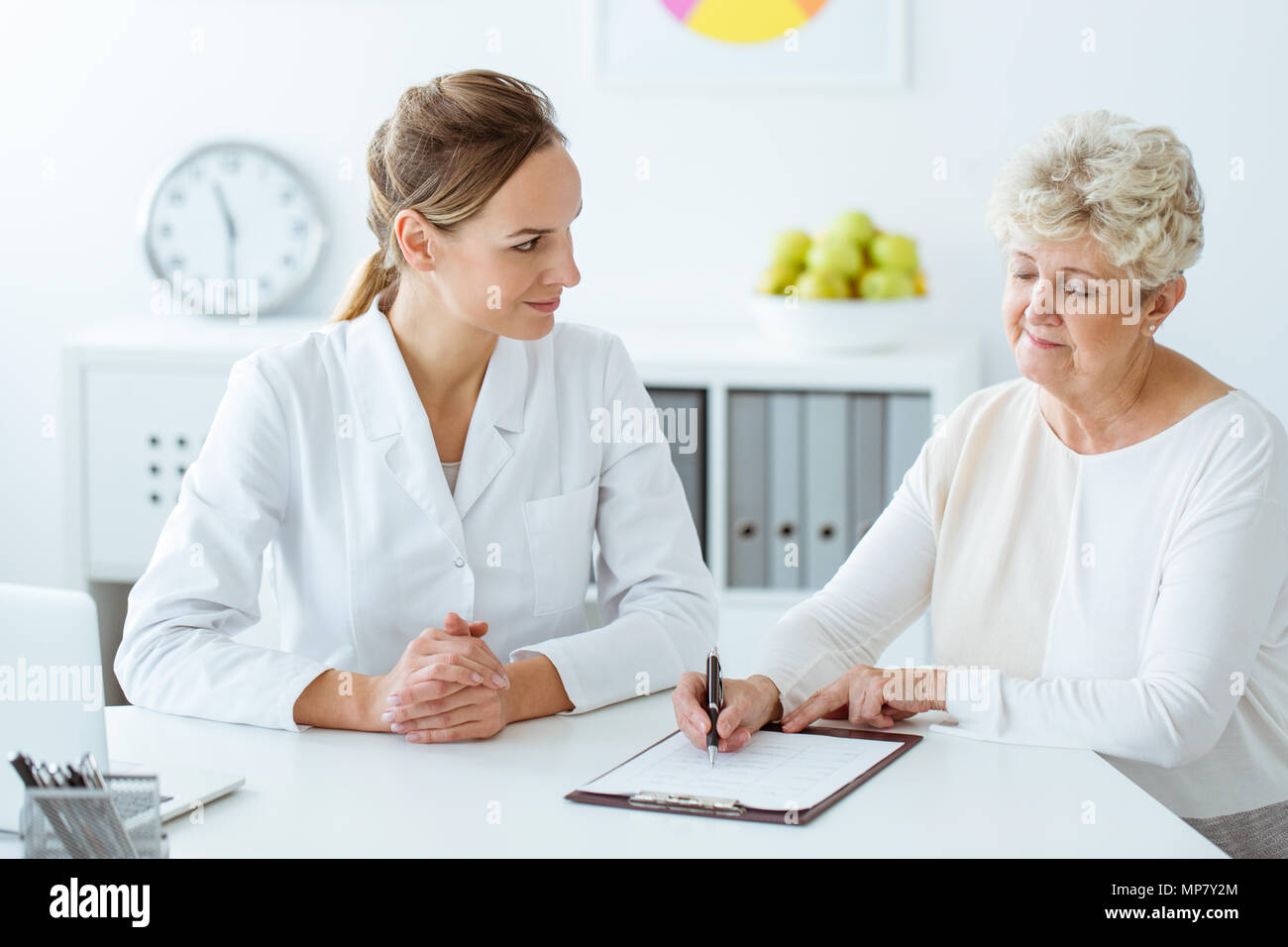 Patient with diabetes writing daily eating habits during a meeting with dietician - Stock Image