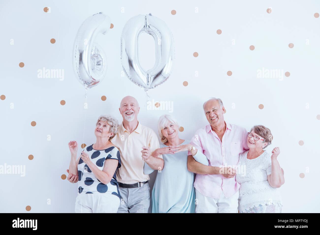 Enthusiastic seniors celebrating elderly woman's birthday with silver balloons Stock Photo