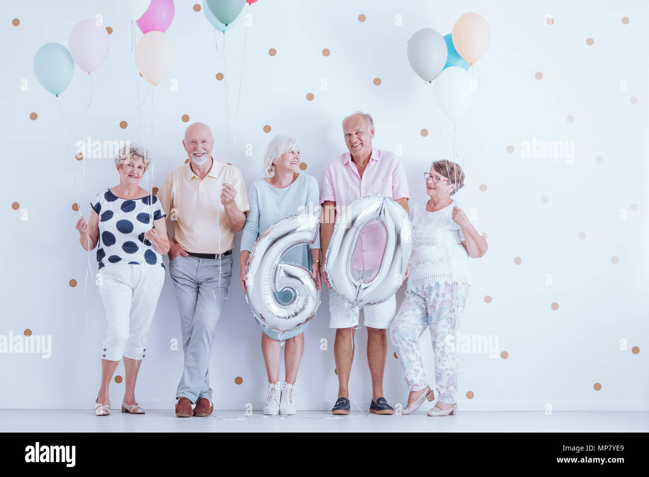 Happy elderly people holding balloons during a birthday party - Stock Image