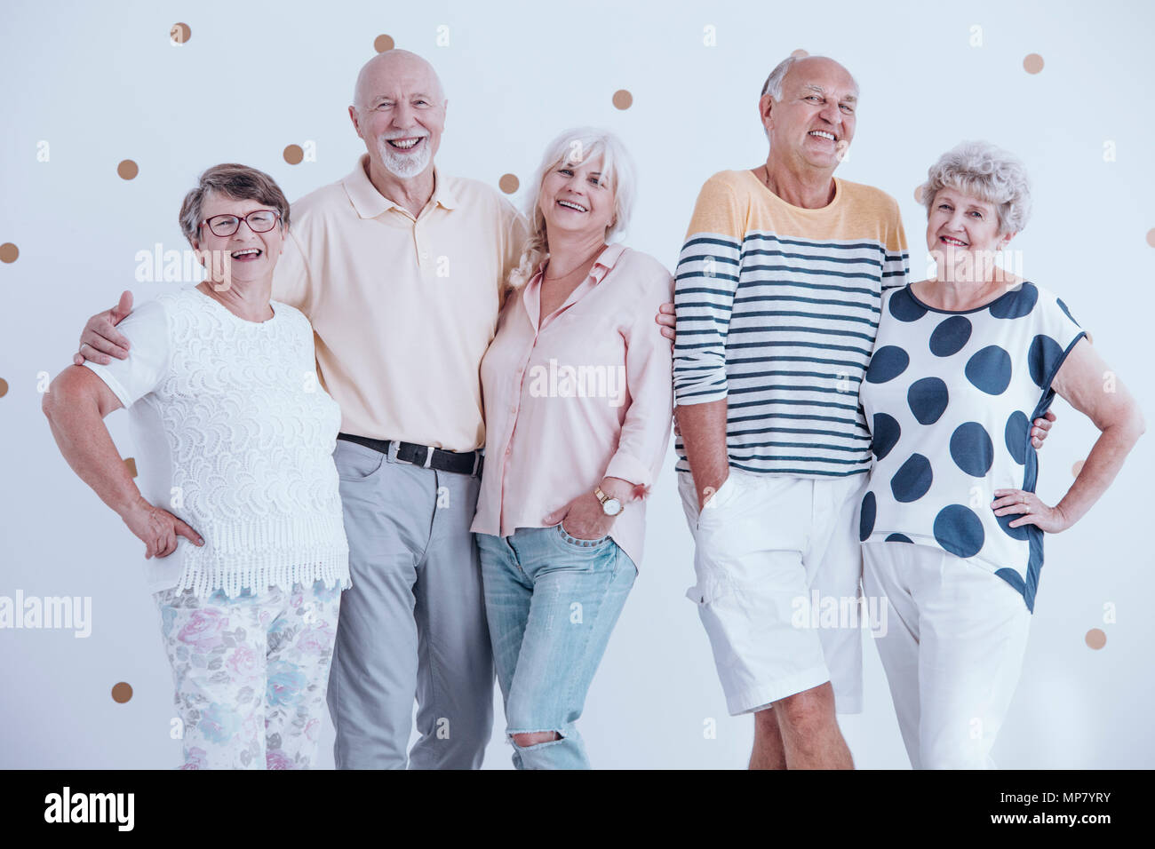 Smiling senior people enjoying birthday party against white wall with gold dots - Stock Image