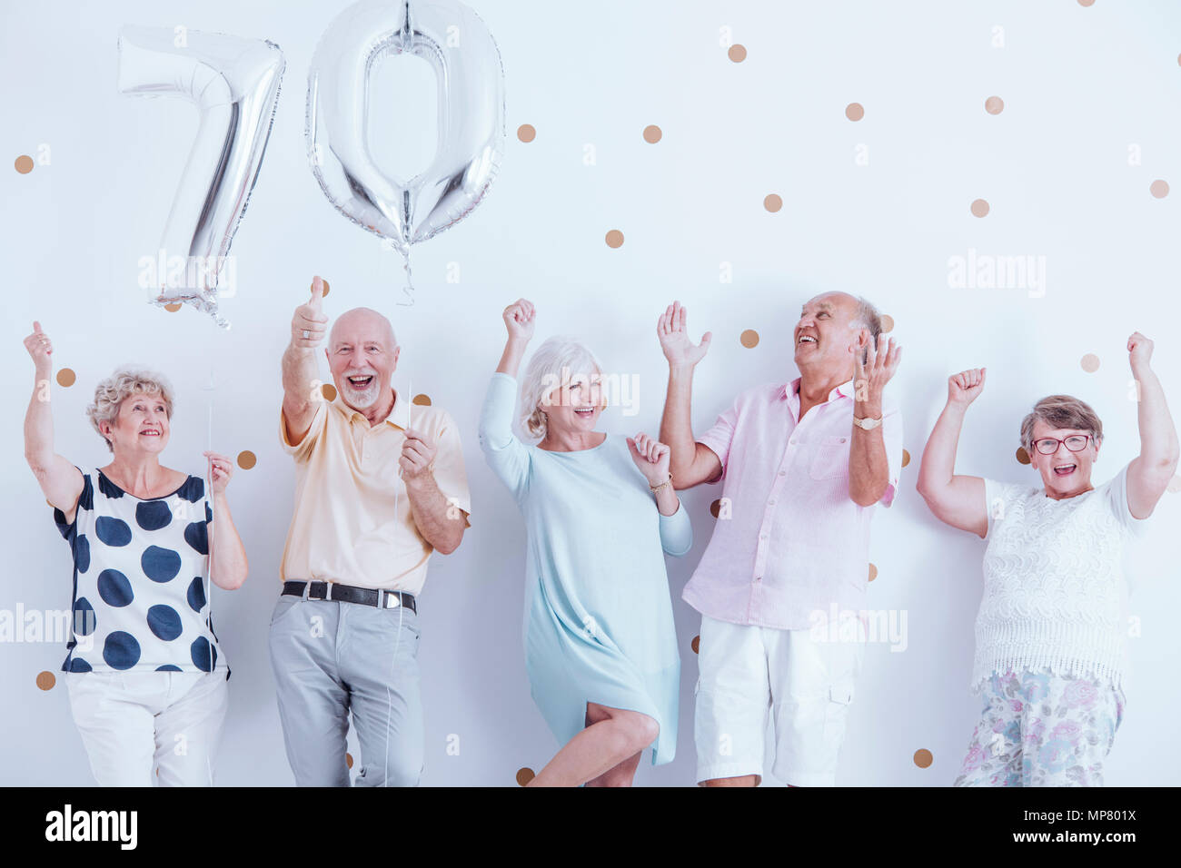 Positive seniors family celebrating grandfather's birthday with silver balloons Stock Photo