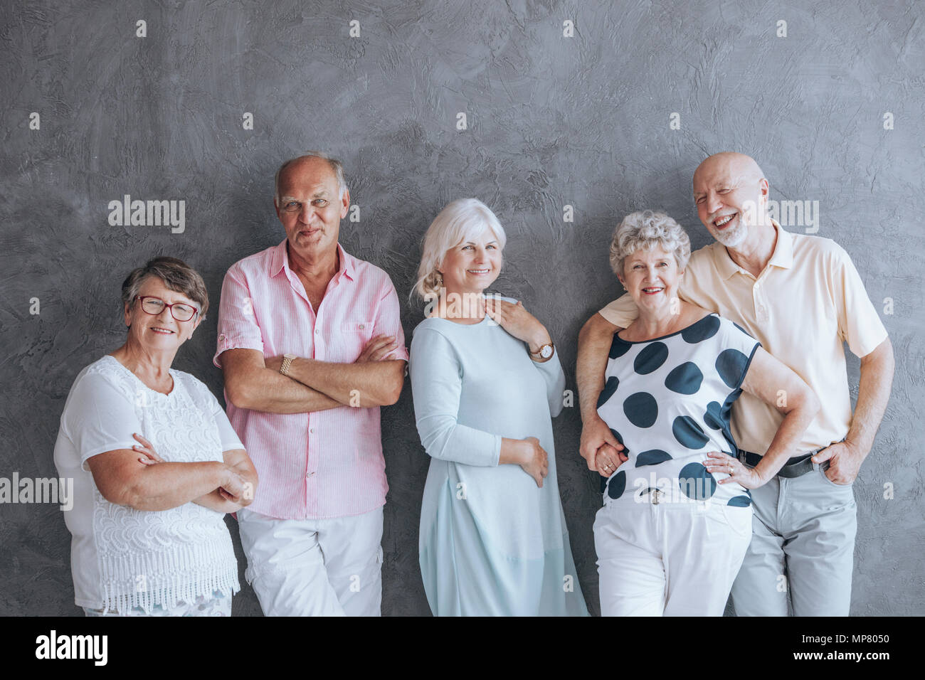 Happy elderly people in casual clothes against concrete wall. Seniors friendship concept Stock Photo