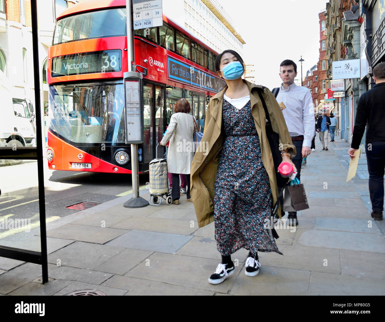 Japanese woman wearing a facemask in Central London, England, UK. - Stock Image