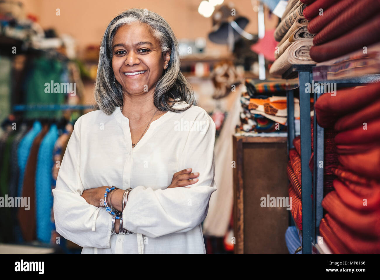 Smiling mature woman standing in her colorful fabric shop - Stock Image