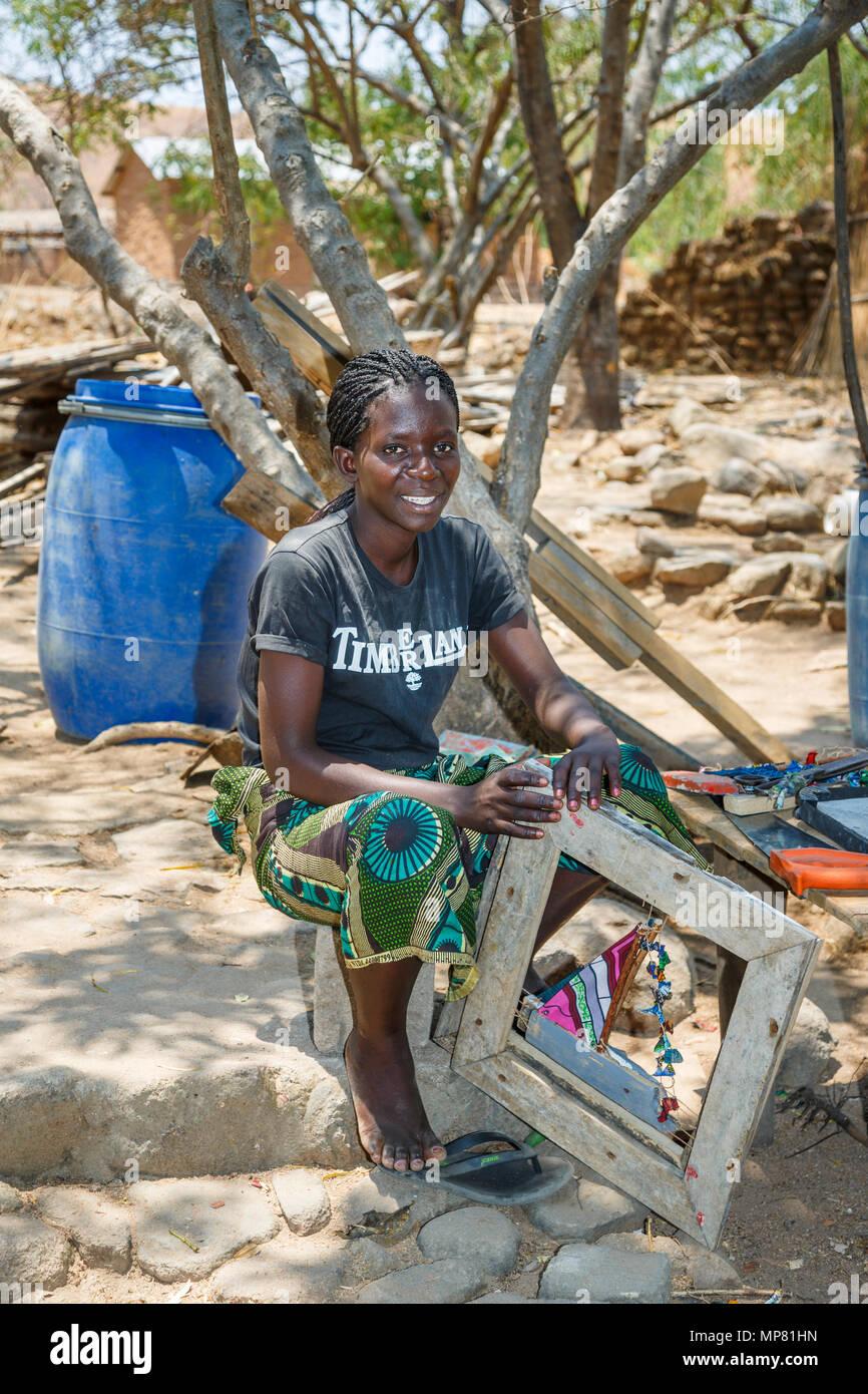 Smiling local African woman with braided hair sitting working outdoors at Katundu creative trade workshop, Likoma Island, Lake Malawi, Malawi, Africa - Stock Image