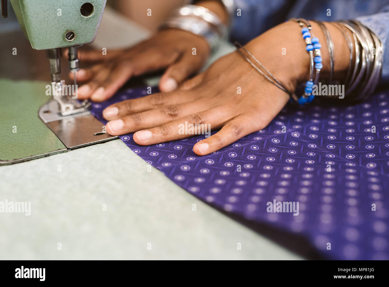 Closeup of a seamstress stitching cloth with her sewing machine - Stock Image