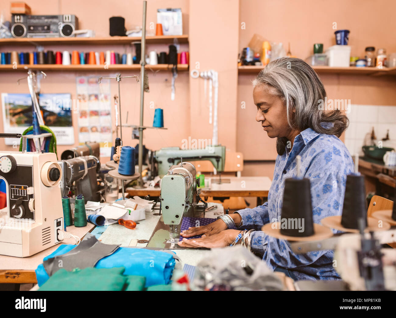 Mature seamstress working in her sewing workshop - Stock Image