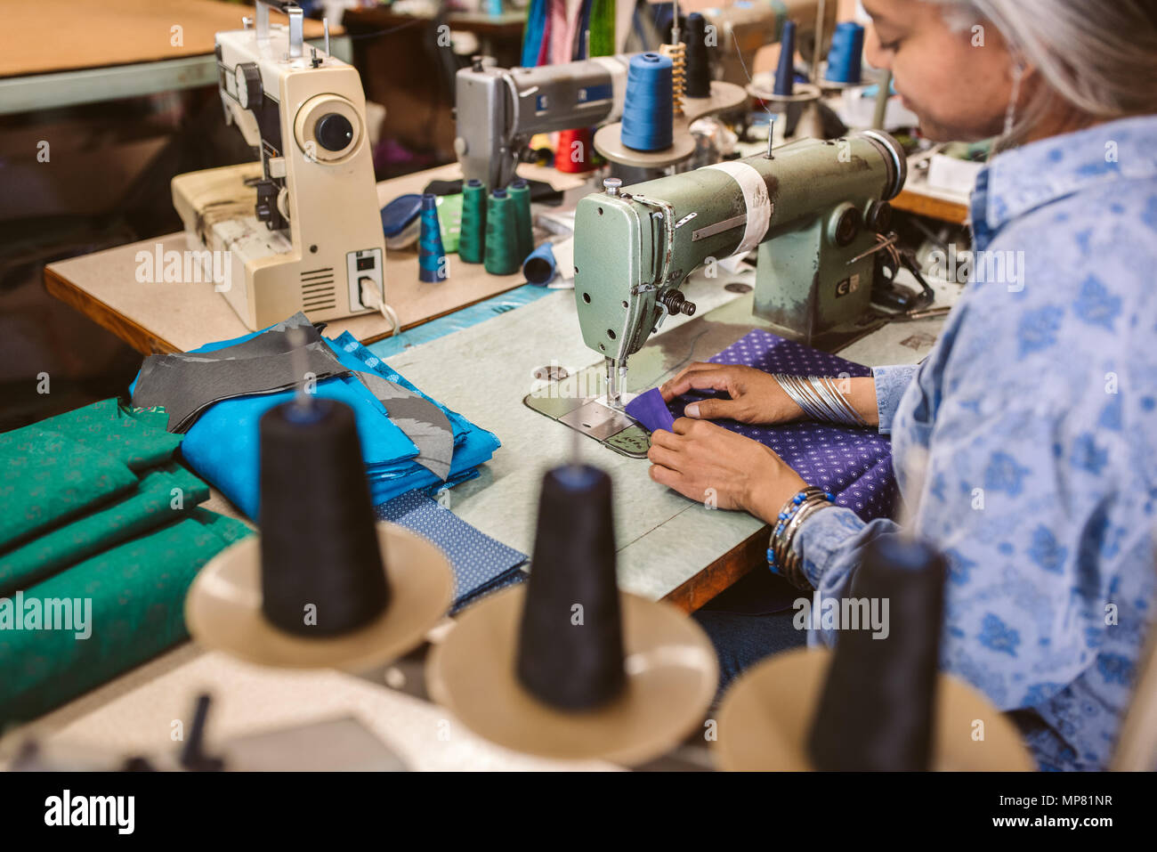 Mature woman working on a sewing machine in her workshop - Stock Image